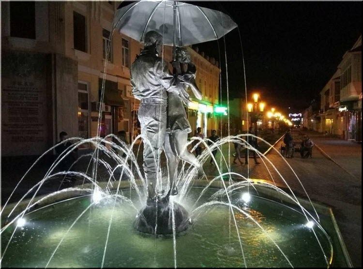 фото фонтана Пара под зонтом ночью