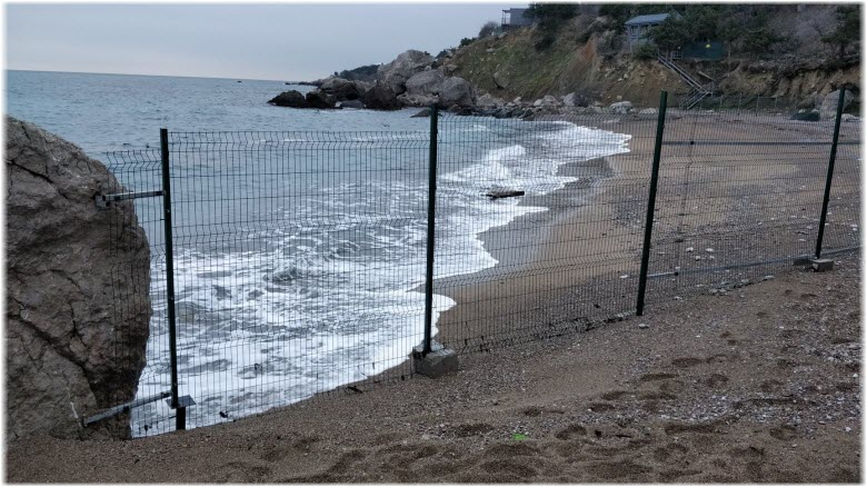 забор, который стоял на пляже Таврида